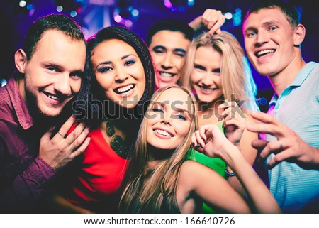 Portrait of happy girls and guys in smart clothes looking at camera at party
