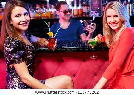 Portrait of happy girls holding cocktails and looking at camera in bar - stock photo