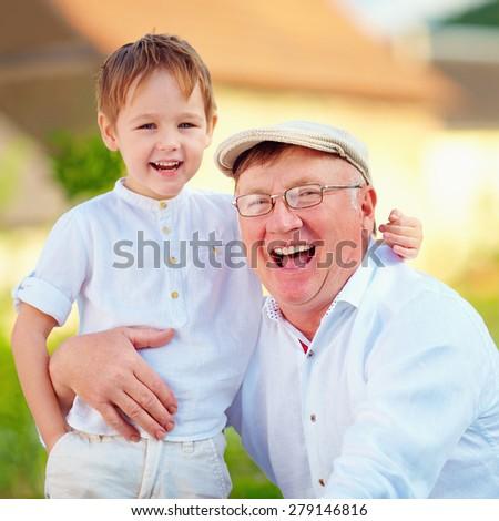 portrait of happy grandpa and grandson, outdoors - stock photo