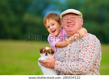 portrait of happy grandpa, grandson and puppy - stock photo