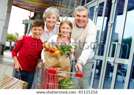 Portrait of happy grandparents and grandchildren near supermarket