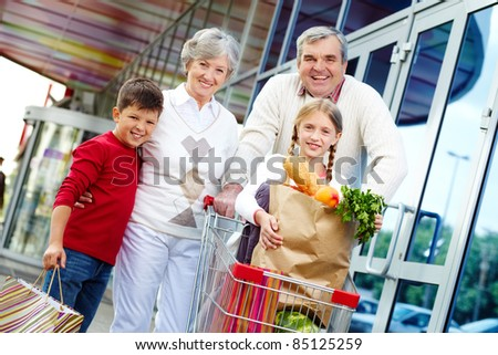 Portrait of happy grandparents and grandchildren near supermarket - stock photo