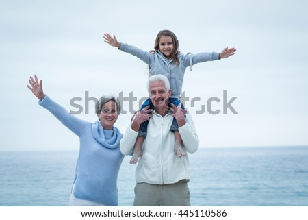 Portrait of happy grandparents and granddaughter with arms outstretched at beach