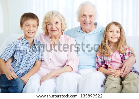 Portrait of happy grandparents with two grandchildren having rest at home