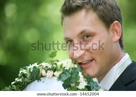 Portrait of happy groom holding bouquet of flowers in a natural environment