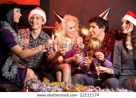Portrait of happy guys and girls enjoying New Year party with champagne and Bengal lights - stock photo