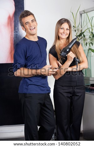 Portrait of happy hairdressers holding scissors and hairdryer in salon - stock photo