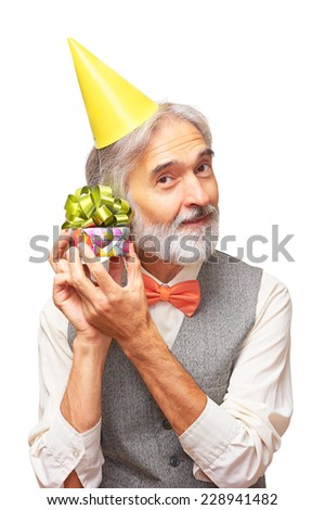 Portrait of happy handsome senior man with a gray beard and orange bowtie in the yellow festive hood holding small present box  in his hands and listening what is in isolated on white background - stock photo