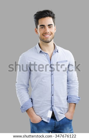 Portrait of happy handsome young man isolated over a gray background - stock photo