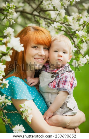 Portrait of happy happy mother ands son in spring garden. Young woman and little boy looking at camera over blooming apple-trees background. Family concept.  - stock photo