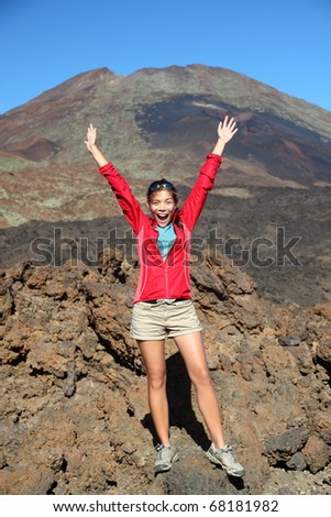 Portrait of happy hiker with arms raised in air with conquered mountain behind. Mountain volcano Pico Viejo on Teide, Tenerife, Canary Islands, Spain. - stock photo