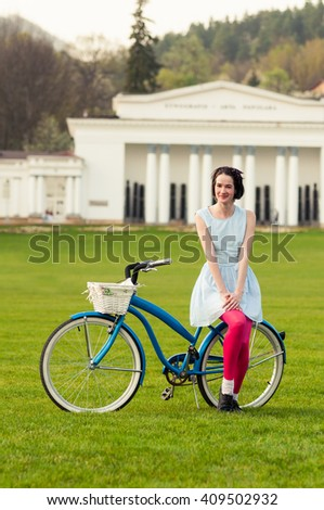 Portrait of happy hipster woman enjoying spring on a bicycle as freetime activity concept - stock photo