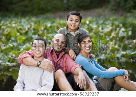 Portrait of happy Hispanic family with two boys outdoors - stock photo