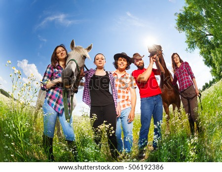 Portrait of happy horseback riders with two horses