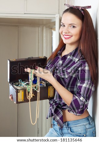 portrait of happy housewife with treasure chest in home