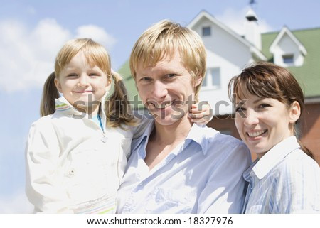 Portrait of happy husband, wife and their daughter somewhere outside - stock photo