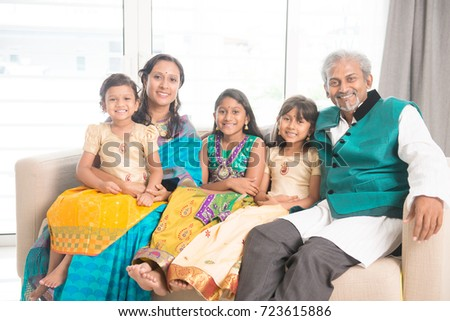 Portrait of happy Indian family in traditional clothes at home, smile at camera. Asian parents and children indoors lifestyle.