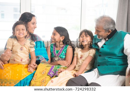 Portrait of happy Indian family talking at home. Asian parents and children indoors lifestyle.
