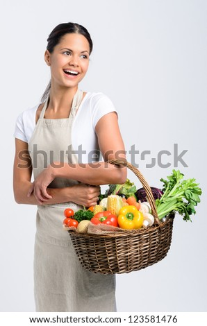 Portrait of happy indian woman holding a basket full of fresh organic vegetables looking away on grey background, promoting healthy diet and lifestyle - stock photo