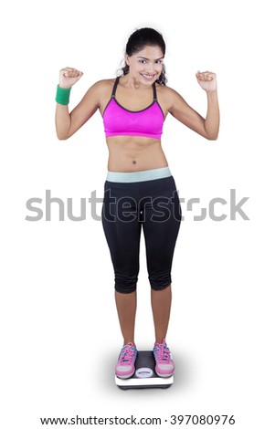 Portrait of happy Indian woman wearing sportswear and standing on weighing scale, isolated on white background - stock photo