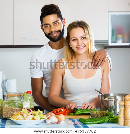 Portrait of happy interracial couple cooking vegetables and laughing in kitchen