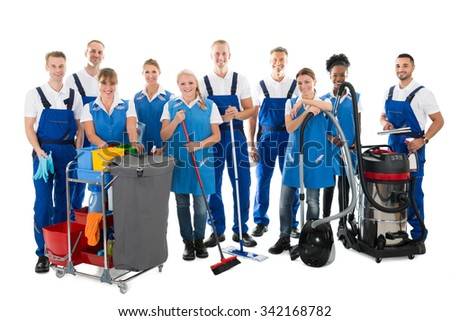 Portrait of happy janitors with cleaning equipment standing against white background - stock photo