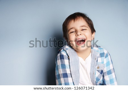 Portrait of happy joyful laughing beautiful little boy on blue background - stock photo