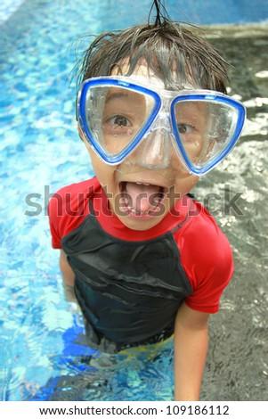 Portrait of happy joyful little boy swimming in the pool - stock photo