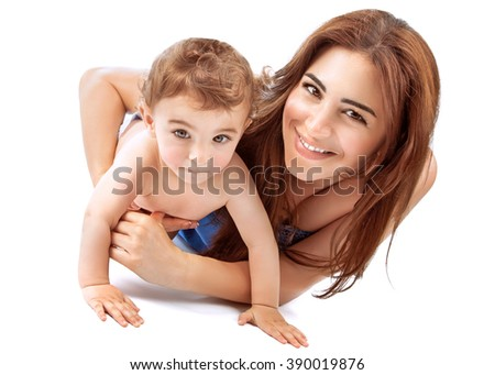 Portrait of happy joyful mother playing with her adorable son, lying down in the studio over white background, enjoying motherhood - stock photo