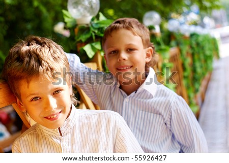 Portrait of happy kid looking at camera with his friend behind - stock photo
