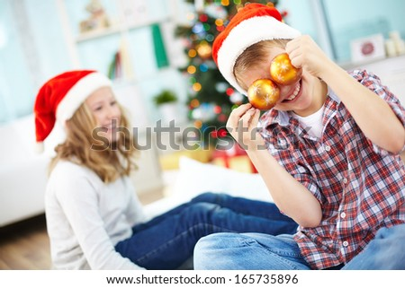 Portrait of happy lad holding decorative toy balls by eyes with his sister on background - stock photo