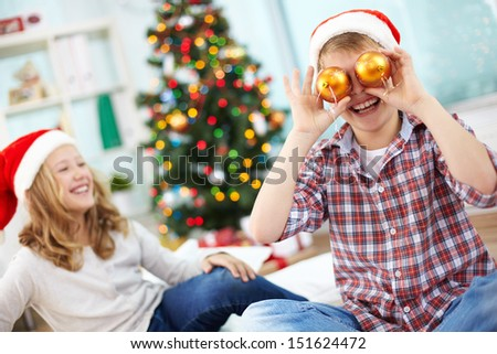 Portrait of happy lad holding decorative toy balls by his eyes and laughing on Christmas evening - stock photo
