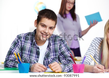 Portrait of happy lad looking at camera during lesson - stock photo