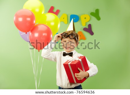 Portrait of happy lad with giftbox putting off funny eyeglasses on birthday party - stock photo
