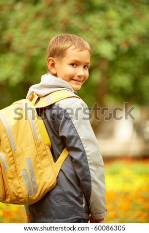 Portrait of happy lad with rucksack on back looking at camera on his way to school - stock photo