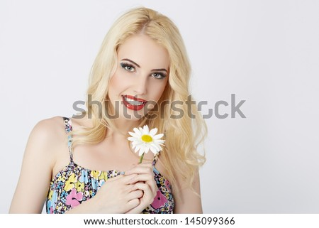 Portrait of happy lady posing with a daisy flower in her hands over bright background. - stock photo