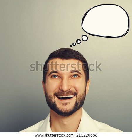 portrait of happy laughing man with empty speech bubble over grey background