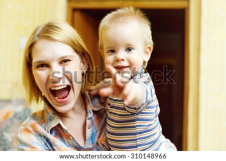 Portrait of happy laughing mother with child on her hands making showing  gesture. - stock photo