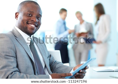 Portrait of happy leader with touchpad looking at camera in working environment - stock photo