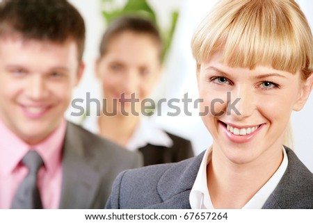 Portrait of happy leader with two employees at background - stock photo