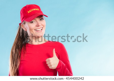 Portrait of happy lifeguard woman girl in red cap with ratownik sign on blue. Accident prevention rescue.