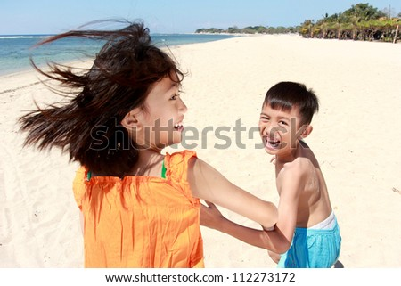 Portrait of happy little boy and girl running in the beach together - stock photo