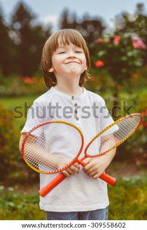Portrait of happy little boy holding badminton rackets while standing on green grass. Warm toned photo - stock photo