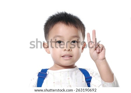 Portrait of happy little boy showing fingers or victory gesture - stock photo