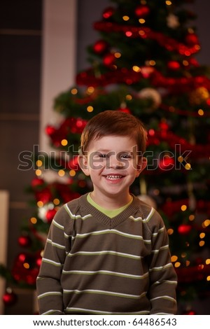 Portrait of happy little boy with christmas tree behind, looking at camera, smiling. ? - stock photo