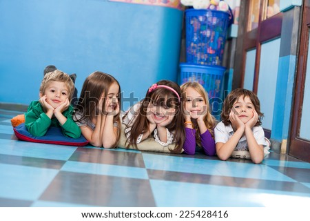Portrait of happy little boys and girls lying on floor in kindergarten