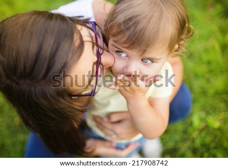 Portrait of happy little daughter and her mother in the park - stock photo
