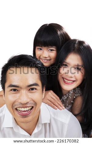 Portrait of happy little family smiling on camera in studio - stock photo