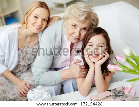 Portrait of happy little girl, her mother and grandmother looking at camera at home