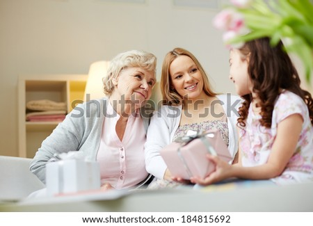 Portrait of happy little girl, her mother and grandmother with giftboxes talking at home - stock photo